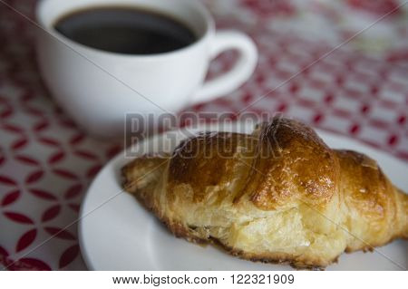 Coffee and croissant for breakfast close up