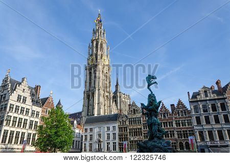 Statue of Brabo throwing the giant's hand into the Scheldt River and the Cathedral of our Lady at Grand Place in Antwerp Belgium.
