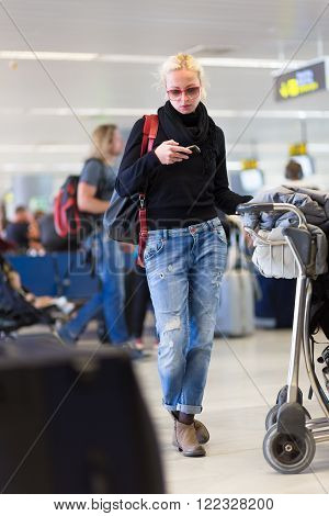 Casual blond young woman using her cell phone while queuing for flight check-in and baggage drop. Wireless network hotspot enabling people to access internet conection. Public transport.