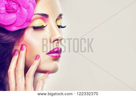 A fashion image model .Trend bright pink makeup . Stylish model girl with pink manicure nails and with  clip on his head   .
