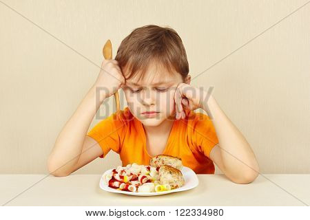 Little discontented boy does not want to eat a pasta with cutlet