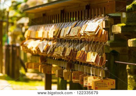 NARA, JAPAN - JUNE 24, 2015: Many small signs or plaques called wooden ema tags carrying written visitor messages and wishes hanging in front of a shinto shrine at the Todai-ji temple complex in Nara Japan. Horizontal