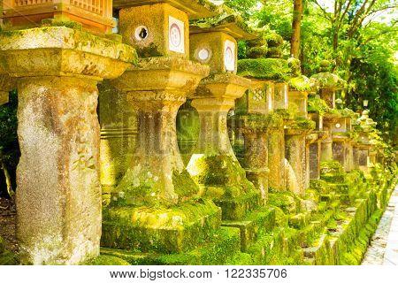 NARA, JAPAN - JUNE 24, 2015: Row of repeating moss covered stone lanterns at Todai-ji temple complex in Nara Japan