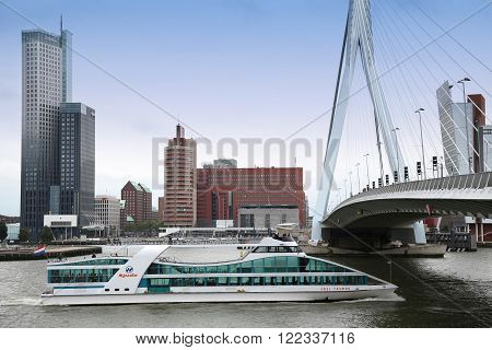 ROTTERDAM THE NETHERLANDS - 18 AUGUST: Rotterdam is a city modern architecture view on Erasmus Bridge (Erasmusbrug) and skyline of Rotterdam with a cruise boat river Maas in Rotterdam Netherlands on August 182015.