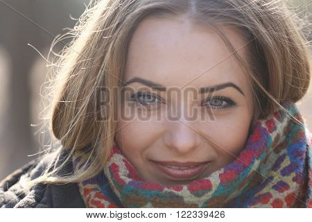 Young Woman's Eyes As She Smiles, Her Hair Blows In The Wind