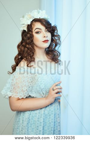 Gentle young woman standing near a window holding a curtain. Soft focus with small depth of field.