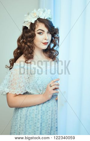 Gentle young woman with overweight standing near the window. Soft focus with small depth of field.