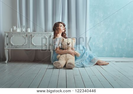 Beautiful woman with overweight sitting on the floor in the room. In her hands she holds toy bear.
