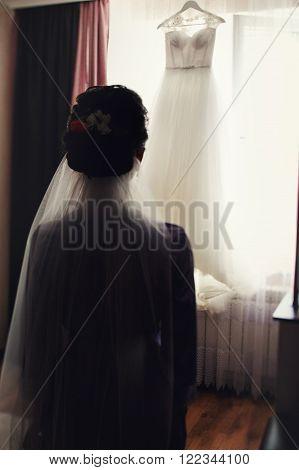 Beautiful Brunette Bride Looking At Hanging White Wedding Dress