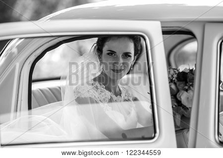 Beautiful brunette bride laughing in luxury white wedding car window reflection b&w