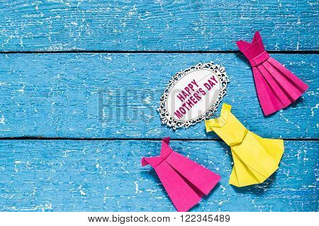 The idea of design for Mother's Day: dresses from paper in the technique of origami on blue wooden background and the inscription: Happy Mother's day