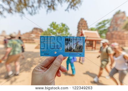 Ayutthaya Thailand - March 16 2016: Hand held the tour ticket of ancient park called Wat Mahathat in Ayutthaya Thailand. The blurred background was tourists walking around temple area.