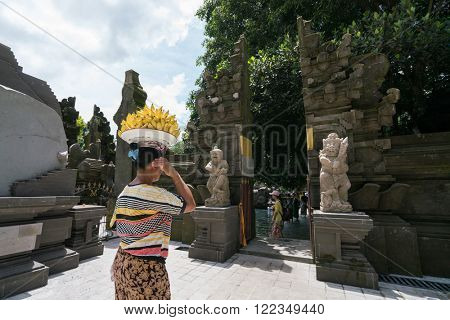 UBUD, BALI - MARCH 14, 2016: A local villager sells banana fruits that she carried in a tray placed on her head to tourists in Pura Tirta Empul (temple).  This temple is a major tourist attraction.