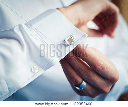 groom in a white shirt, wear stud on sleeve.