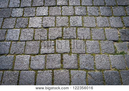 Stone paving dark quadrate texture in old town. Abstract structured background.