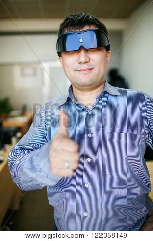 Man in glasses of virtual reality shows thumb up