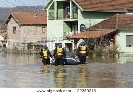 KRALJEVO, SERBIA - MARCH 8. 2016: Rescuers transport the flood victims after heavy rain and the river Morava flooded at Kraljevo, suburbs Grdica, on 8th March 2016.
