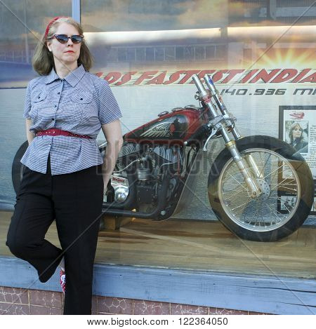 BISBEE, ARIZONA, FEBRUARY 25: The historic Lowell district on February 25, 2016, in Bisbee, Arizona. A model dressed 50s style poses by a refurbished vintage Indian motorcycle in historic Lowell Arizona.
