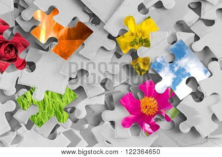 Pile of gray puzzle parts with several parts made as images of nature