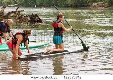 ATLANTA, GA - JULY 2015:  A young woman kneels on a paddleboard as she gets a push into the Chattahoochee River on a hot summer day in Atlanta, GA on July 25, 2015.