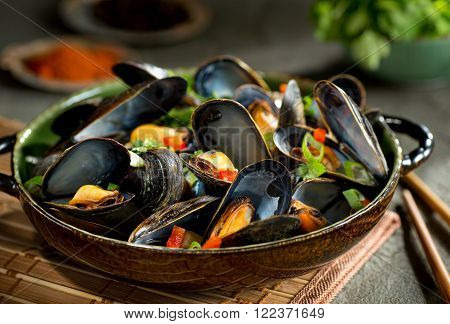 Delicious asian style steamed mussels with red pepper green onion and coriander in a coconut broth.