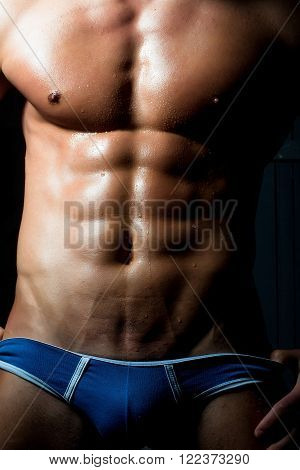 Male sporting beautiful sexual young muscular bare torso of athlete macho with strong abdominal and pectoral muscles dressed in trendy blue underwear closeup studio vertical picture poster
