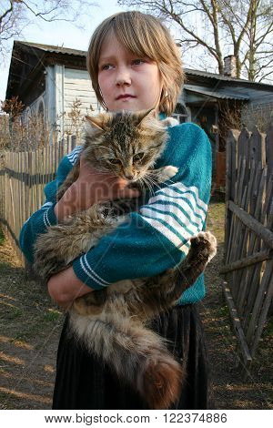 Lipovec village Tver region Russia - May 5 2006: Podol village Tver region Russia - May 5 2006: Pupil second class of general education elementary school Natasha Dmitrieva 8 years old holds big fluffy cat standing in street near rural school.