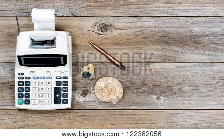Overhead view of an adding machine and paper roll on stressed wood with stone fossils. Obsolete technology concept.