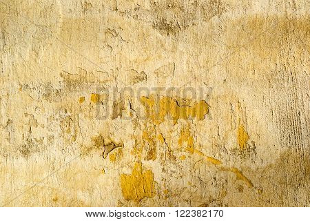 Yellow old dirty concrete cracked wall texture or background