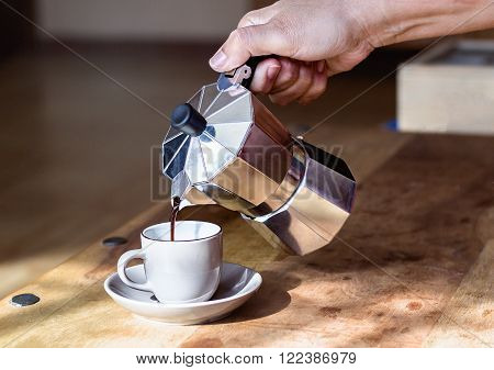 Close-up of  hand holding metal coffee maker while pouring coffee on cup