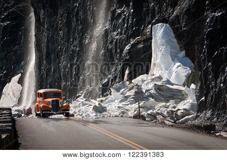 Antique car on a mountain road covered with crushed glacier