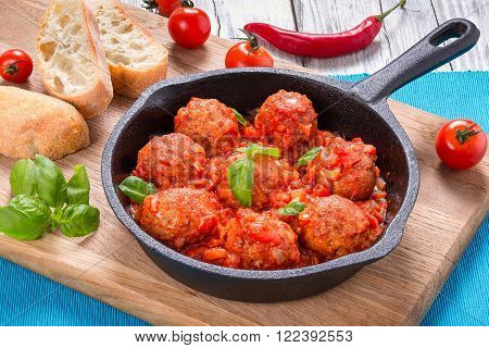 homemade meatballs smothered in a marinara tomato sauce with basil