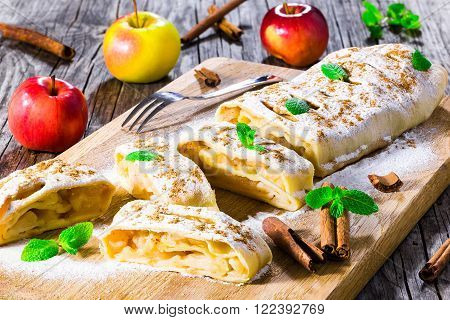 homemade apple strudel with powdered sugar and mint leaves.