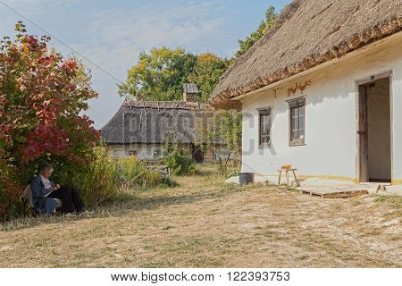 Kiev Ukraine - October 06 2015: Elderly woman - caretaker in museum of Architecture and Life Pirogovo resting in the shade