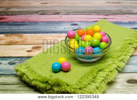 Assorted gum balls on a green napkin.  Space for text.