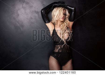Blonde sexy lady with glamour makeup and long curly hair posing in studio. Elegant woman wearing black sensual lingerie.