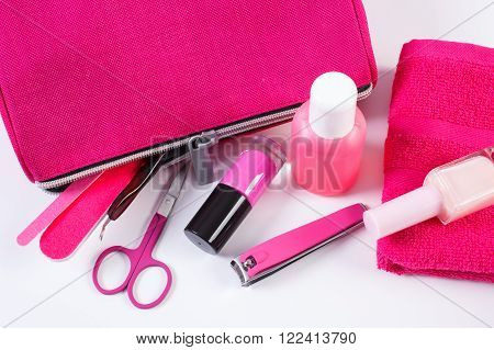 Cosmetics and accessories for manicure or pedicure, pink bag cosmetic, nail file, nail polish and remover, scissors, nail clippers, fluffy towel, concept of nail care