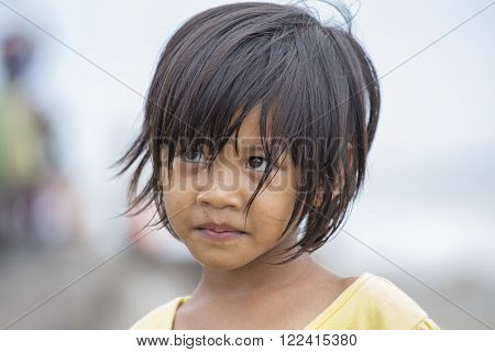 KUTA, BALI, INDONESIA - MARCH 13, 2015 : Unidentified portrait of a little indonesian child at the streets