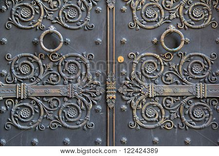 Gorgeous detail in heavy metal doors, with elaborate scrollwork and large knockers that make someone's arrival heard.
