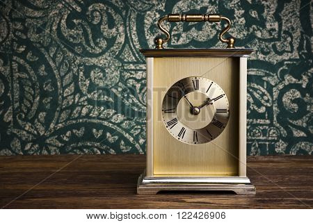 Antique clock on wooden background (time 13-54)