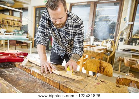 Craftsman using sanding paper on a guitar neck in a workshop for wood. Hard working man with tattoo and beard working with musical instruments.