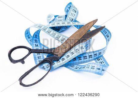 A scissors is cutting a tape measure
