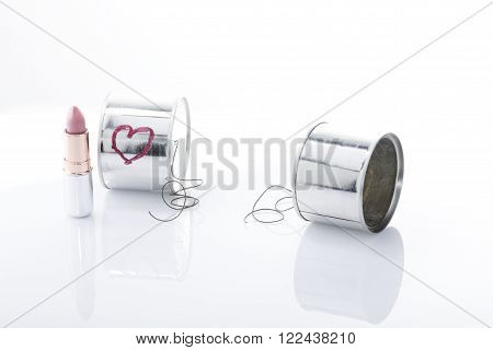 two cans with a wire broken and one lipstick. One of them with a heart painted. It is a metaphoric photo about couple break up concept.