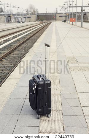 black suitcase left alone on platform at trainstation