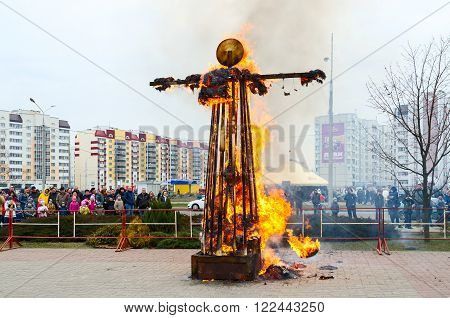 GOMEL BELARUS - MARCH 12 2016: Unidentified people in the crowd behind the barrier are looking at burning down effigy of Shrovetide during Shrovetide celebrations