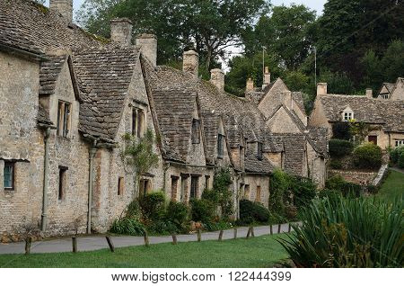 The Arlington Row honey coloured weavers cottages in the town of Bibury in Gloucestershire in the Cotswolds England UK. The houses were built in 1380.