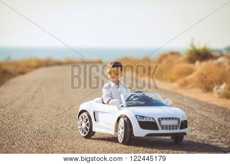 The young driver,a boy with brunette short hair,mirrored sun glasses yellow,in white shirt posing on a mountain road against the sea and clear sky,sitting in a posh toy car white color in the fresh summer air ** Note: Shallow depth of field