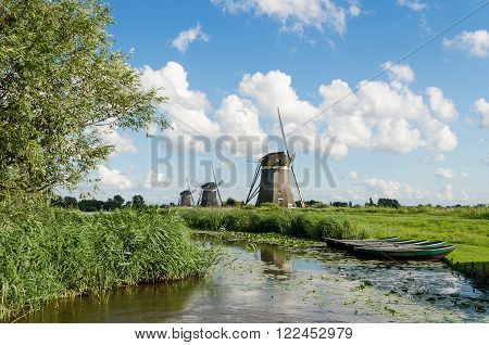 Landscape in Holland with three windmills and a canal with reeds and rowboats.