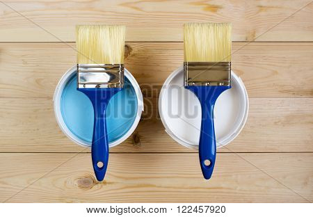 two brush and a white and blue paint on wooden boards in banks