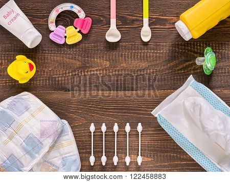 Japanese diapers wet wipes soap baby powder cream tither cotton buds spoons soother and duckling on dark brown wooden background with copy space. Flat lay or top view